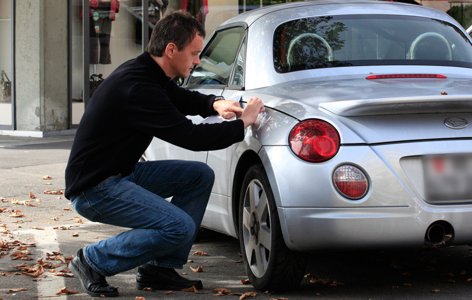 Man applying scratches stickers on a car